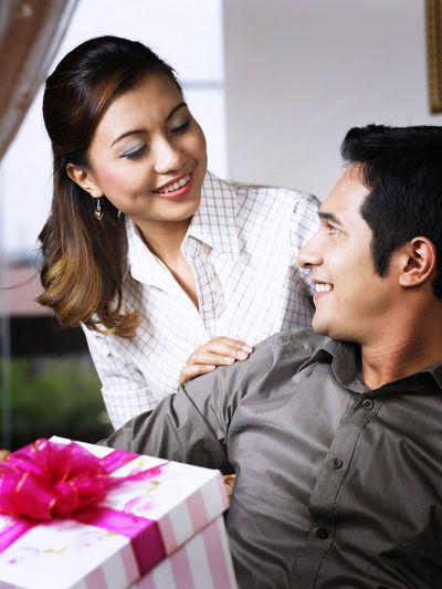 asian couple giving a present Asian  At Home Celebration Christmas Couple Fun Happy Love Relationship Ribbon Romantic Valentine's Day  Anniversary Birthday Bonding Boyfriend Celebration Event Cheerful Gift Girlfriend Giving Present Smile Surprise Togetherness