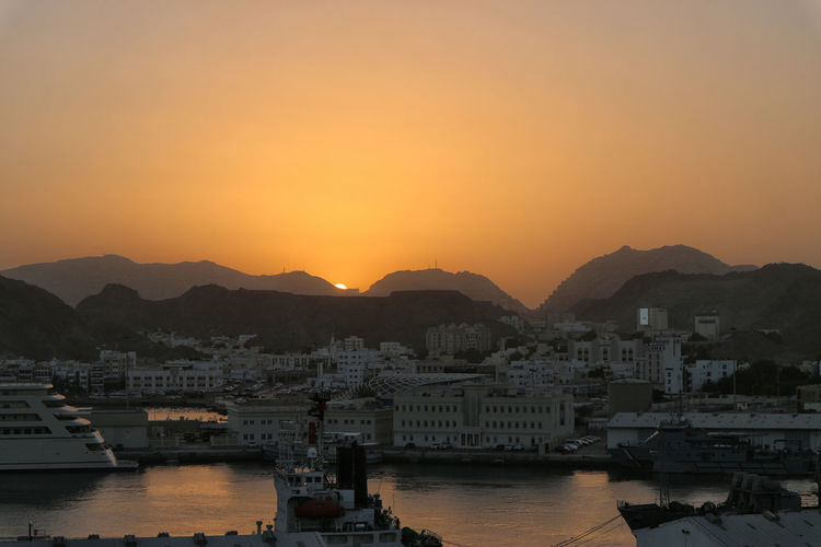 View Of City At Waterfront During Sunset
