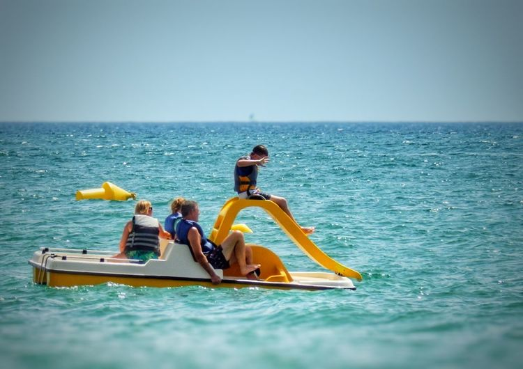 Blue Boat Clear Sky Escapism Horizon Over Water Leisure Activity Men Mode Of Transport Nautical Vessel Pedalo Pedalo With Slide Pedalos Peopleon A Pedalo Scenics Sea Togetherness Tranquil Scene Transportation Vacations Water Waterfront Yellow Pedalo