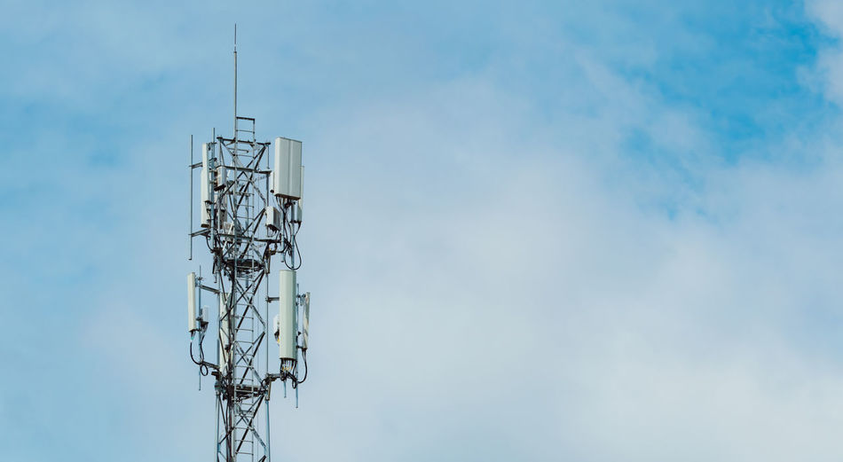Telecommunication tower with blue sky and white clouds background. antenna on blue sky.