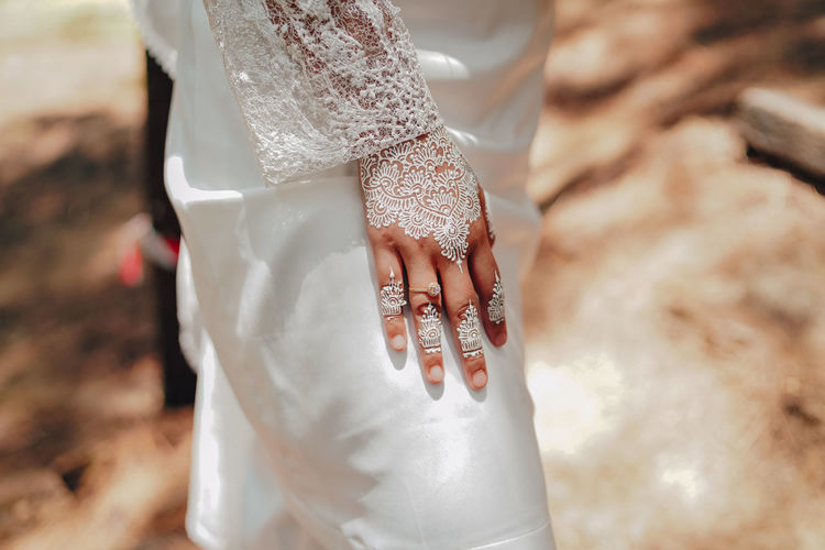 Midsection of bride wearing wedding dress while standing outdoors