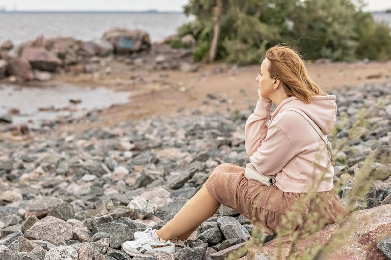 Rear view of woman sitting on rock