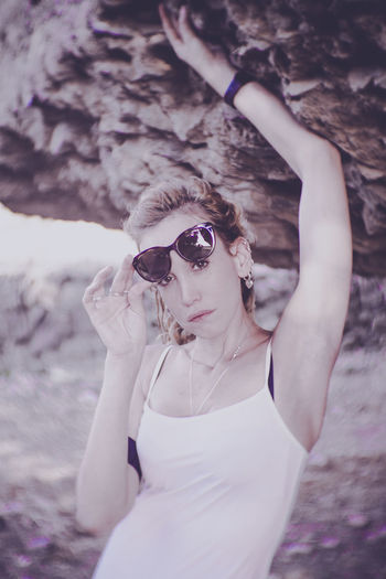 Portrait Of Beautiful Woman Holding Sunglasses While Standing Outdoors