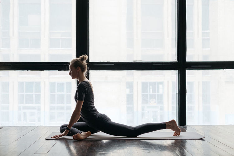 Women practice yoga in the loft Full Length One Person Yoga Lifestyles Real People Exercising Flexibility Wellbeing Practicing Window Relaxation Exercise Healthy Lifestyle Indoors  Stretching Young Adult Wood Contemplation Flooring Women Young Women Yoga Yoga Pose