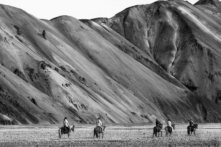 Rear View Of People Riding Horses At Landmannalaugar