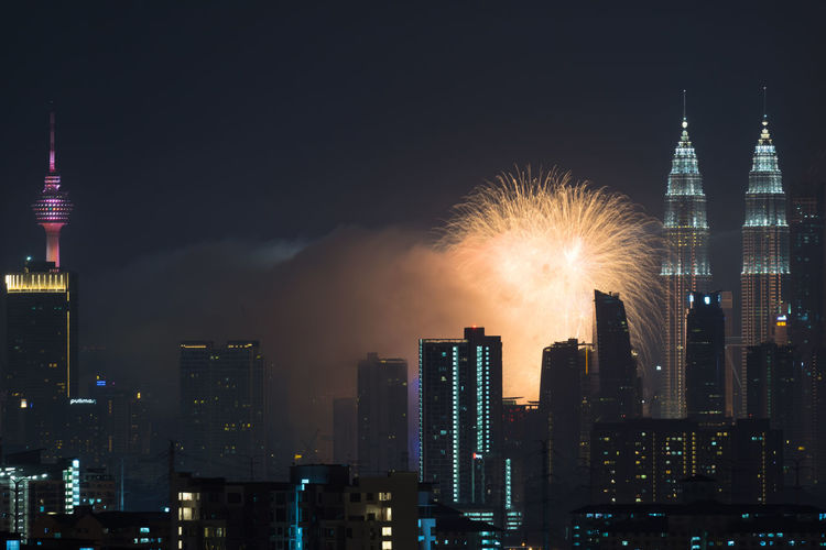 Firework display over city lit up at night