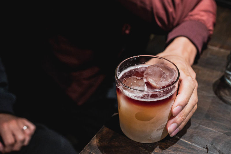 High angle view of hand holding drink on table