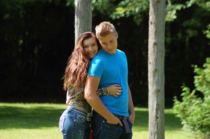 Young couple standing amidst tree trunks at park