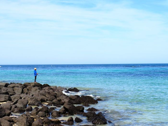 Man standing on rocks at sea against sky