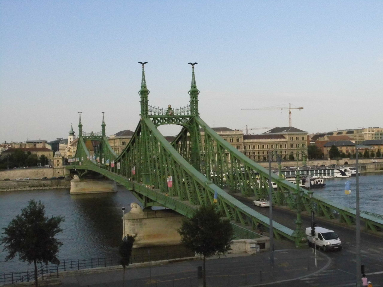 architecture, water, built structure, outdoors, river, clear sky, bridge - man made structure, travel destinations, sky, transportation, day, building exterior, no people, tree, nature, city, chain bridge