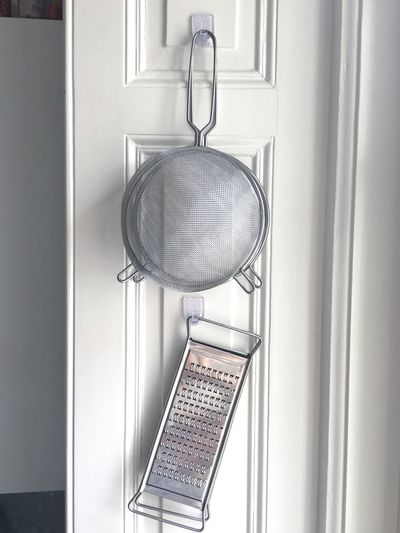 Strainer and grater hanging on window at home