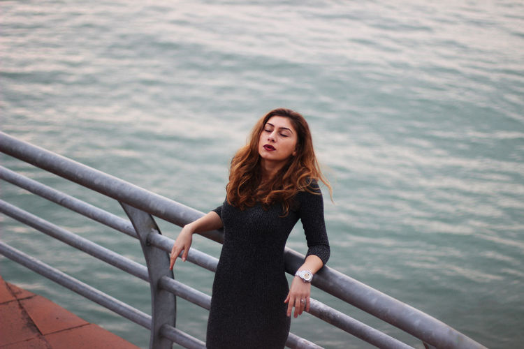 High Angle View Of Woman Leaning On Railing At Observation Point Against Sea