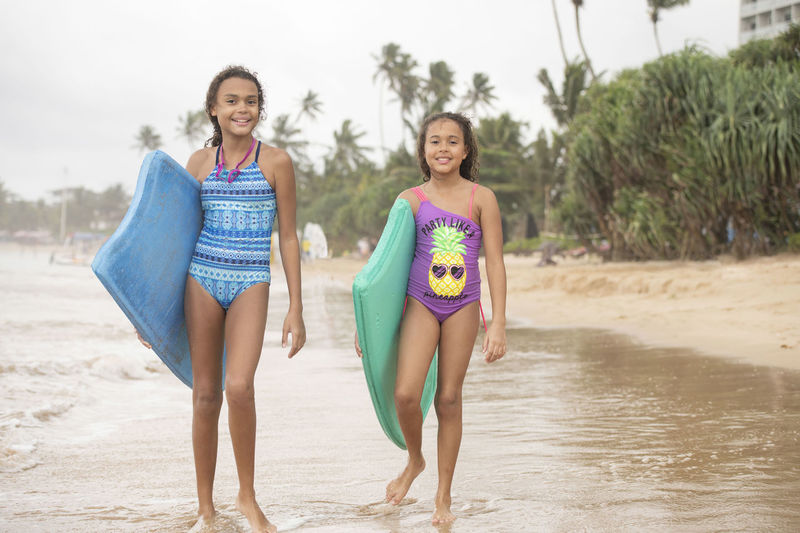 Two beautiful young mixed race sister girls walking on the beach wearing swim wear laughing with boogie boards Sister Beach Bi-racial Child Boogie Boards Emotion Front View Full Length Happiness Land Leisure Activity Looking At Camera Mixed Race Kids Outdoors Portrait Positive Emotion Real People Smiling Swimwear Togetherness Trip Tropical Island Two People Vacations Water Women