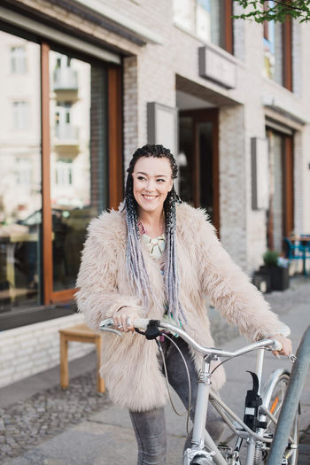Hip young happy young woman parking her bicycle on a street Braids Cool Dressed Up Hair Attractive Bicycle Bike Casual Clothing City Coat Daylight Fashionista First Eyeem Photo Fur Hairstyle Influencer Lifestyles Parking Real People Street Warm Clothing Women Young Adult