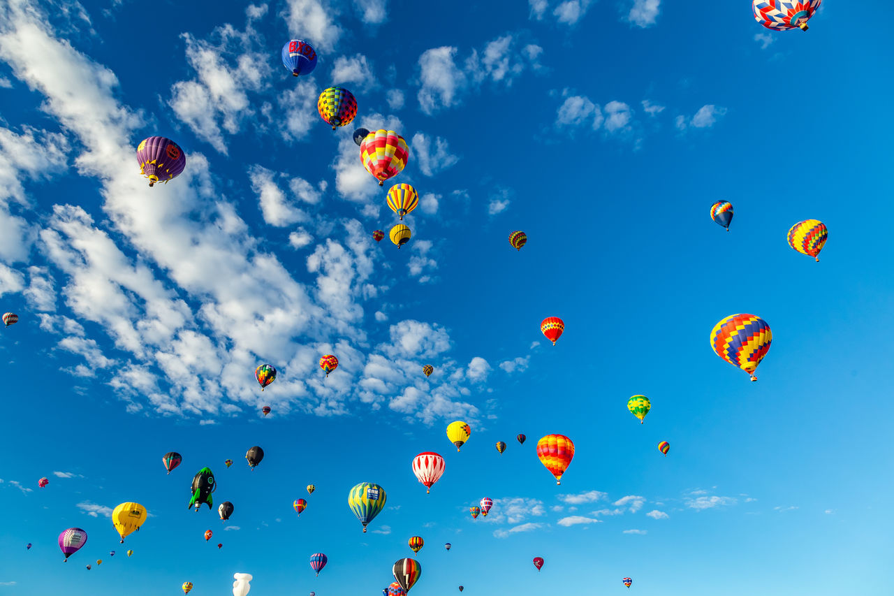 sky, low angle view, cloud - sky, balloon, mid-air, nature, multi colored, flying, blue, no people, day, celebration, large group of objects, ballooning festival, hot air balloon, outdoors, beauty in nature, air vehicle, sunlight, lightweight
