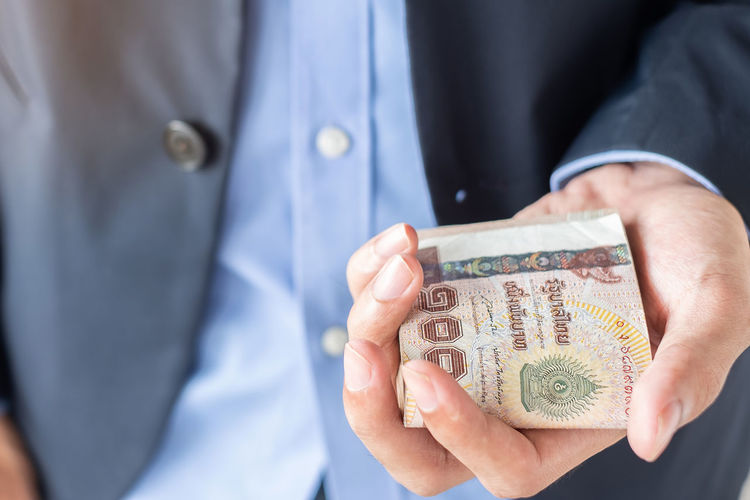 Midsection of businessman holding paper currencies