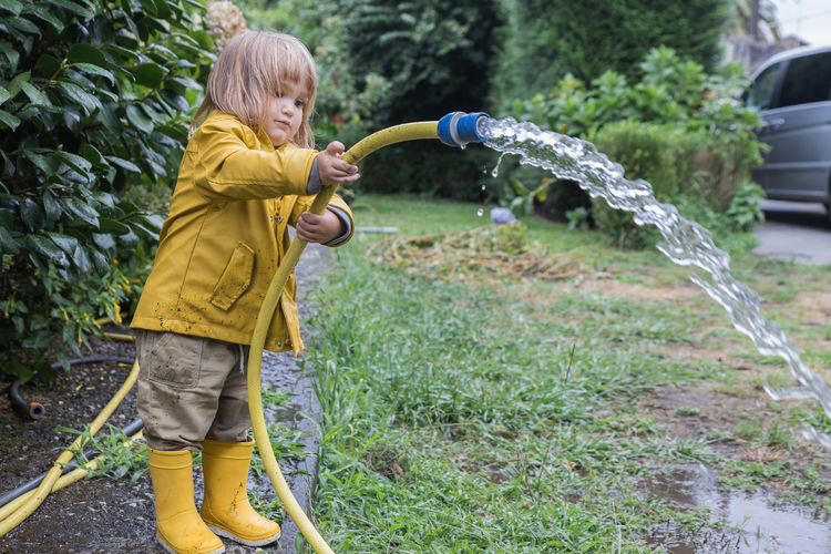 Full length of boy playing with plants in water