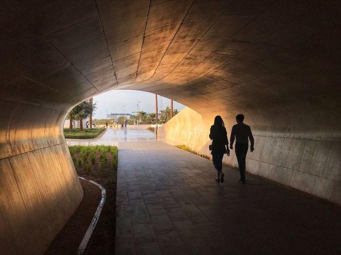 Rear view of people walking on footpath in tunnel
