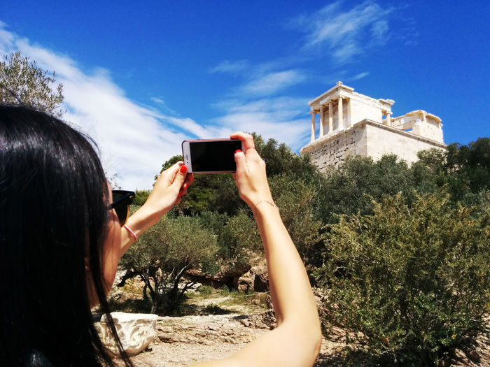 Woman Photographing Parthenon Temple Against Sky