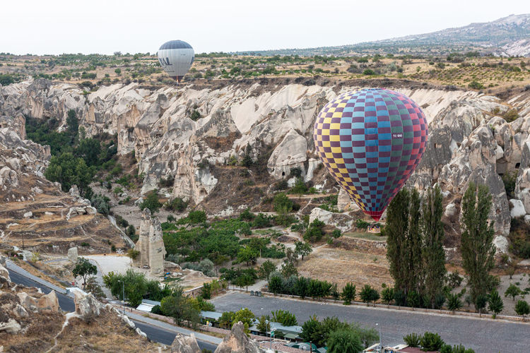 High angle view of hot air balloon flying over mountain