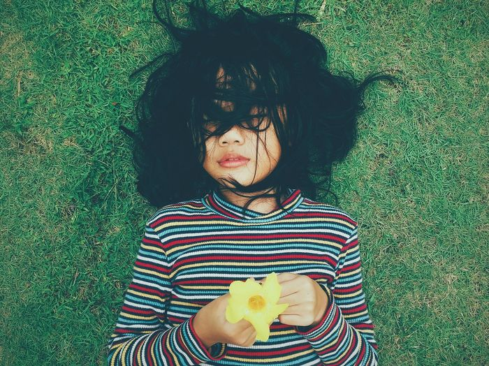 High angle view of woman with messy hair lying on grass