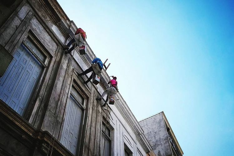 Building Exterior Low Angle View Architecture Only Men Built Structure Outdoors Adults Only Occupation Adult Working Sky Day Clear Sky Hardhat  People Manual Worker Headwear Industry Painting Hanged Hanged Out Hangedman