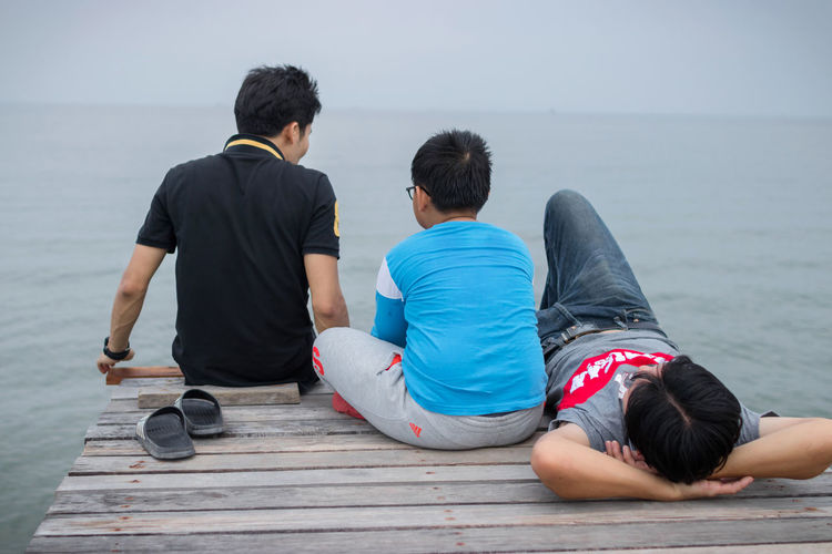 Father with sons relaxing pier by sea against sky
