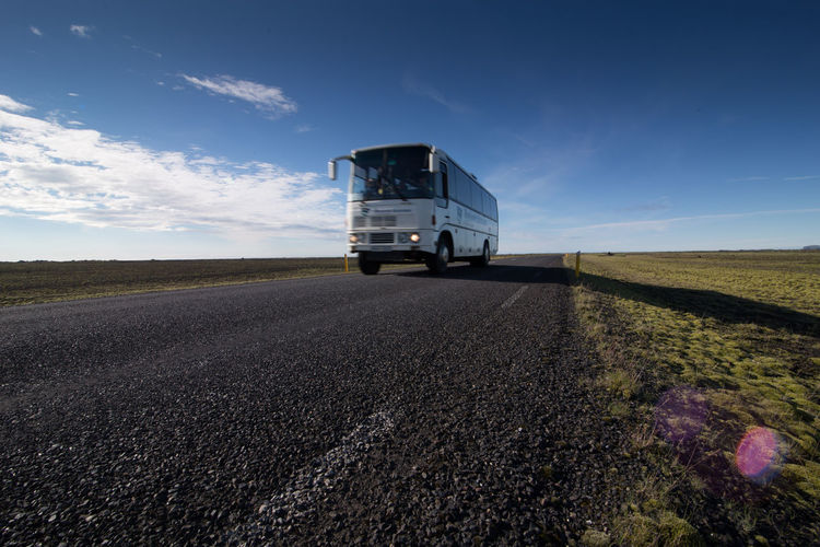 Bus moving on road amidst landscape against sky