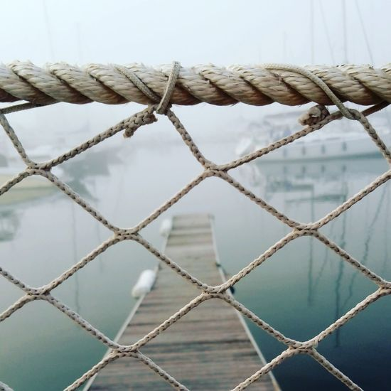 Metal Outdoors Day Protection No People Sky Exclusion Nature Harbor Boats Fog Foggy Foggy Day Wiew Grey Clouds Tightrope Relaxing Freaky Man And Sea Sea Water Tranquility Nautical Vessel
