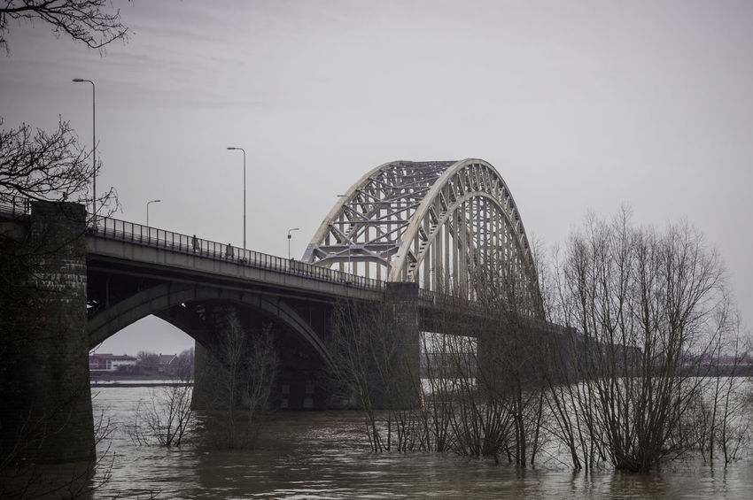 Nijmegen The Netherlands Waalbrug Nijmegen Arch Arch Bridge Arched Architecture Bare Tree Betuwe Black And White Photography Bridge Built Structure Connection Day Holland Long Nature No People Outdoors River Sky Transportation Tree Water Waterfront