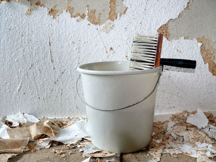 Brush and bucket against damaged wall