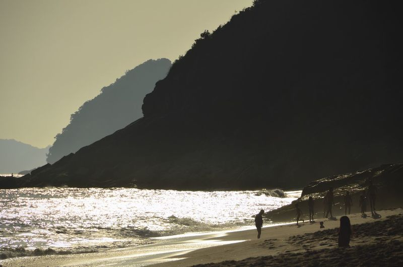 Silhouette people on beach by mountain against sky
