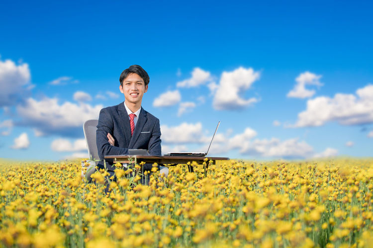 Portrait of smiling businessman sitting with laptop on field
