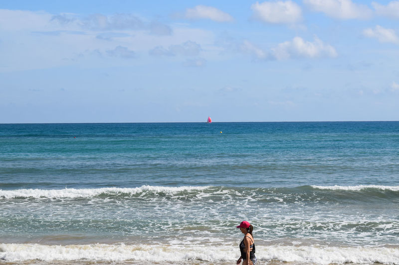 red hat and red sail Red Color Sailboat Sailing Sail Hat Wave Water Wave Sea Beach Clear Sky Full Length Sand Standing Summer Red Seascape Coastline Beach Holiday Coastal Feature Ocean Coast
