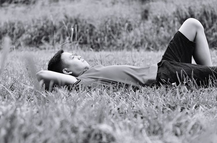 Grass Lying Down Field Lying On Back One Person Relaxation Meadow Leisure Activity Full Length Young Adult Outdoors Happiness Day Hands Behind Head Real People Nature Childhood Portrait
