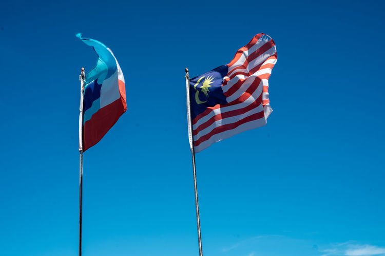 Malaysia and sabah flags waving against blue sky in the background.