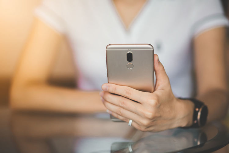 Adult Business Marketing Communication Connection Front View Hand Holding Human Hand Indoors  Lifestyles Marketing Midsection Mobile Phone One Person Portable Information Device Selective Focus Smart Phone Technology Telephone Text Messaging Using Phone Wireless Technology