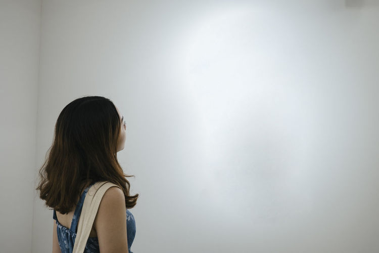 Rear view woman looking at wall