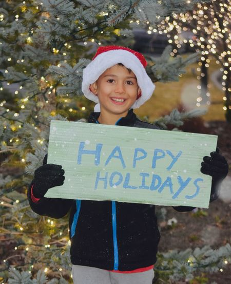 Boy Holding Sign Wishing You A Happy Holiday Season Elf Wearing Santa Hat Lights On Trees Little Boys NAUGHTY Or NICE  Santa's Helpers Young Boy Cheerful Childhood Elves Holding Merry Christmas One Person Outdoors Popular Holiday Concepts Photos Images And Collections Seasonal Decorations Seasons Greetings Signs And Banners Smiling Snowing Snowing Outdoors In Winter Time Standing Text Winter Time