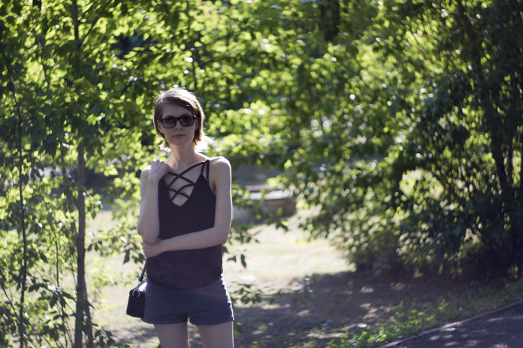 Portrait of young woman wearing sunglasses standing against trees