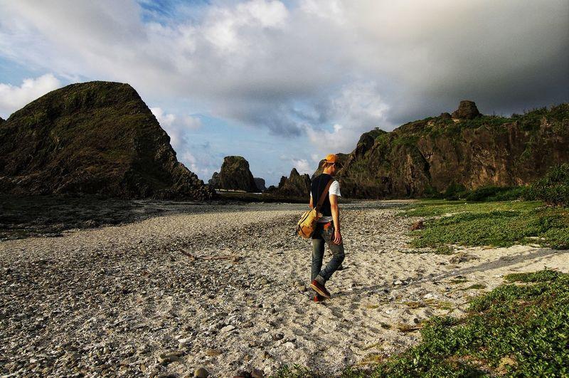 Man walking by rock formations at green island