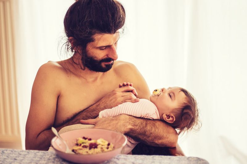 baby sleeping in daddy's arms at breakfast Daddy Dad Breakfast Home Chilling Sleeping Nap Holding Hands Fatherhood  Indoors  Young Adult Shirtless Real People Home Interior People Two People Child Young Sitting Baby Togetherness Bonding Childhood Facial Hair