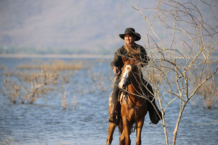 horse, travel, adventure, cowboy, western, horseback riding, horse riding, wanderlust, globetrotter, lifestyle Outdoors Young Adult One Animal One Person Horse Day Lifestyles Clothing Domestic Leisure Activity Mammal Domestic Animals Animal Themes Hat Vertebrate Real People Animal Nature Water