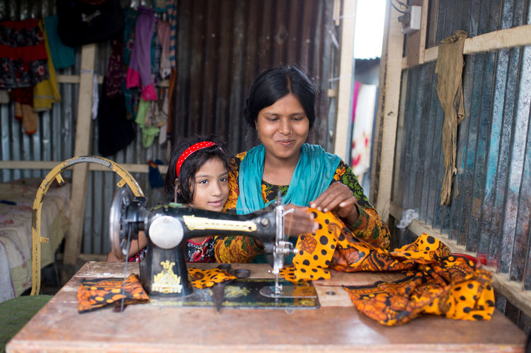 RePicture Motherhood a mother who works and makes a living to support her daughters education. She has opened a tailor shop inside her own house in a slum. Inspiring Bangladesh Dhaka Women Empowerment