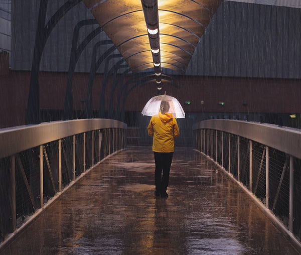 Rear view full length of woman with umbrella standing in footbridge during rainy season at night