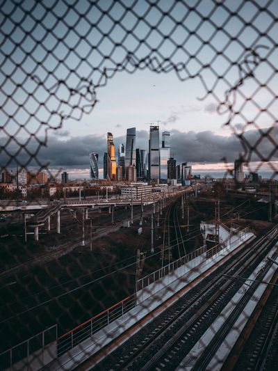 Railroad tracks seen through fence against cityscape during sunset