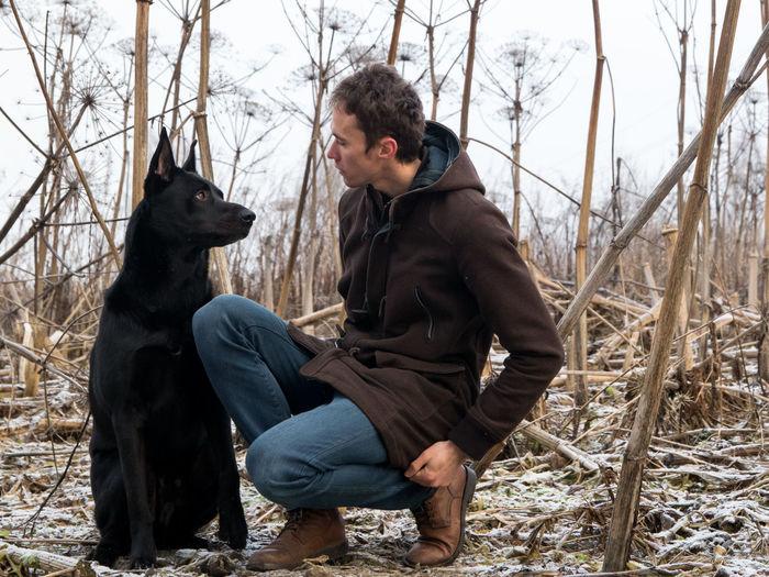Man crouching by dog on land
