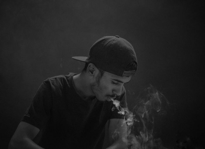 Side view of man smoking cigarette against black background