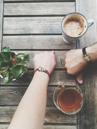 Close-up of people hands wearing bracelets by drinks on wooden table