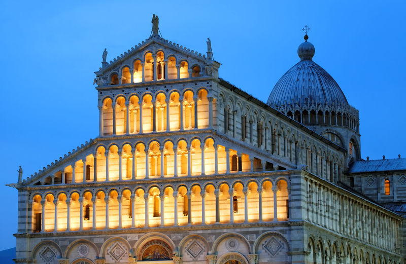 Low angle view of illuminated pisa cathedral against clear sky at dusk